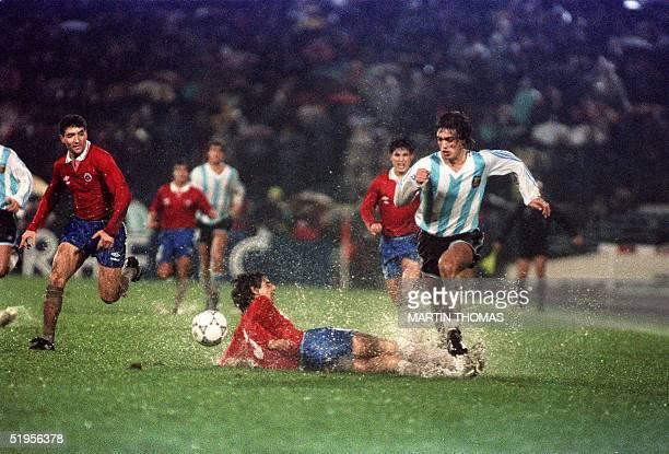 Gabriel Batistuta de Argentina se lleva la pelota superando al chileno Lizardo Garrido que cae en el agua durante el partido por la Copa America...