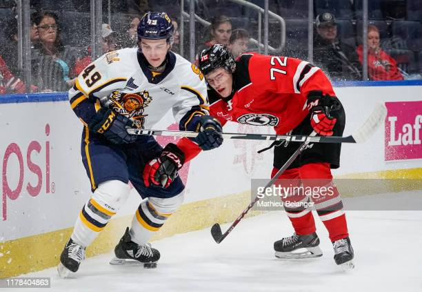 Gabriel Belley-Pelletier of the Shawinigan Cataractes and Pierrick Dube of the Quebec Remparts battle for the puck during their QMJHL hockey game at...