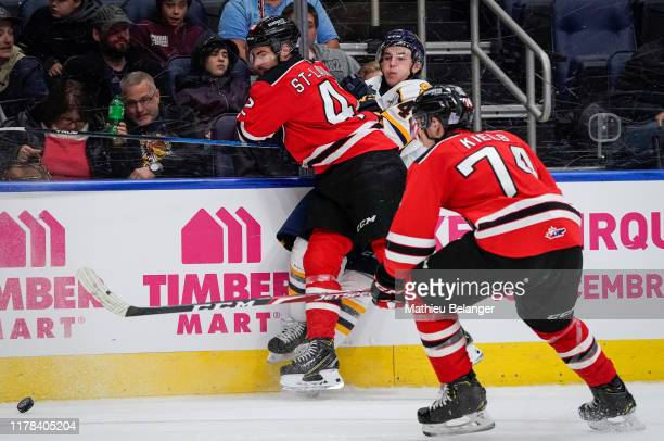 Gabriel Belley-Pelletier of the Shawinigan Cataractes is hit by Edouard St-Laurent of the Quebec Remparts during their QMJHL hockey game at the...