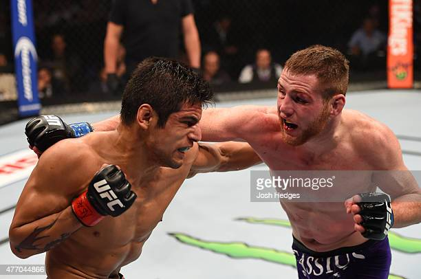 Gabriel Benitez of Mexico exchanges punches with Clay Collard of the United States in their featherweight bout during the UFC 188 event at the Arena...