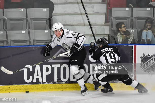 Gabriel Bilodeau of the Gatineau Olympiques skates the puck against Alex BarreBoulet of the BlainvilleBoisbriand Armada during the QMJHL game at...