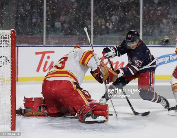 Gabriel Bourque of the Winnipeg Jets gets a shot off on David Rittich of the Calgary Flames during the 2019 Tim Hortons NHL Heritage Classic at...