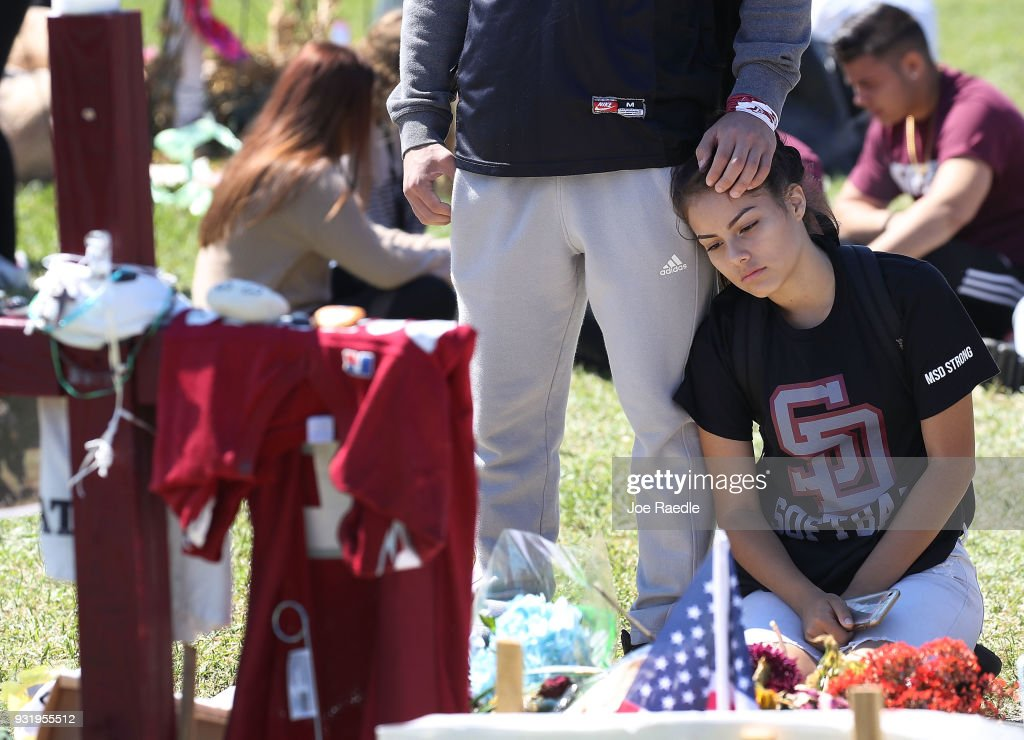 Gabriel Constantino and Nikki Healey (R) from Marjory Stoneman Douglas High School stand together at a memorial after walking out of school to honor the memories of 17 classmates and teachers that were killed during a mass shooting at the school on March 14, 2018 in Parkland, Florida. The students joined others around the country to mark the one-month anniversary of the shooting with a National Walk out day.