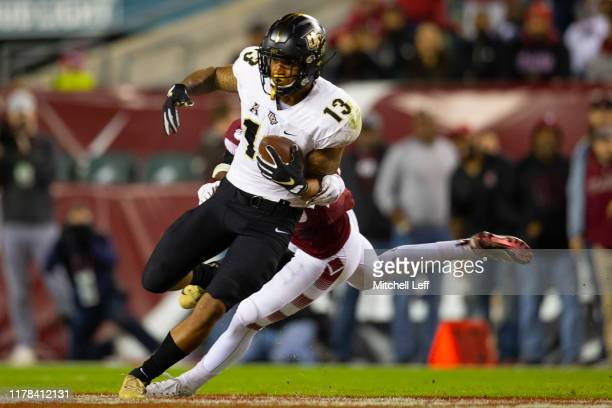 Gabriel Davis of the UCF Knights catches a pass and runs for the ball against Ayron Monroe of the Temple Owls in the second quarter at Lincoln...