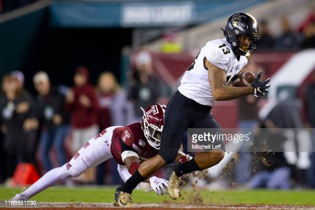 Gabriel Davis of the UCF Knights catches a pass and runs the ball against Ayron Monroe of the Temple Owls in the second quarter at Lincoln Financial...