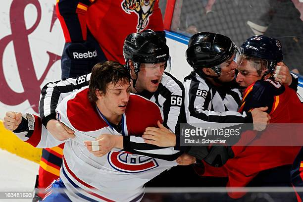 Gabriel Dumont of the Montreal Canadiens tangles with Drew Shore of the Florida Panthers while NHL Linesman Scott Driscoll and Ryan Galloway keep the...