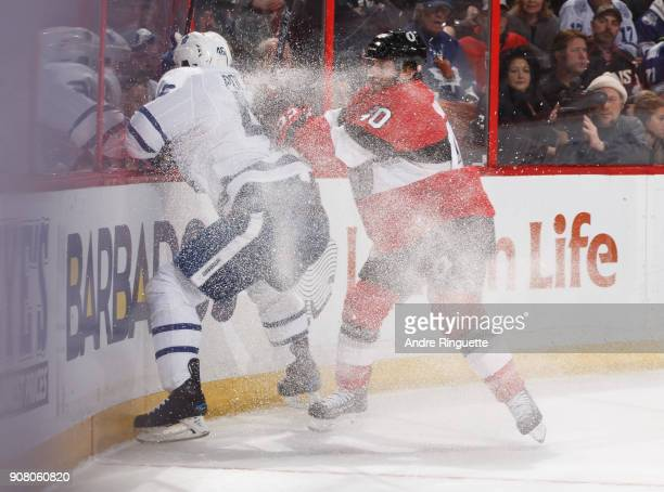 Gabriel Dumont of the Ottawa Senators body checks Roman Polak of the Toronto Maple Leafs into the end boards at Canadian Tire Centre on January 20...