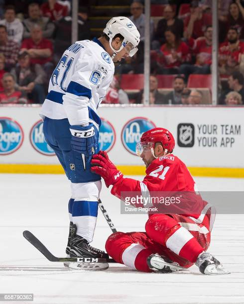Gabriel Dumont of the Tampa Bay Lightning knocks down Tomas Tatar of the Detroit Red Wings during an NHL game at Joe Louis Arena on March 24 2017 in...