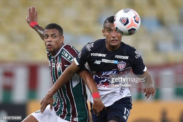 Gabriel Fuentes of Junior competes for the ball with Caio Paulista of Fluminense during a match between Fluminense and Junior as part of Group D of...