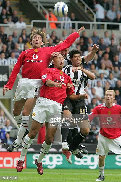 Gabriel Heinze and Mikael Silvestre of Manchester United clash with Albert Luque of Newcastle United during the Barclays Premiership match between...