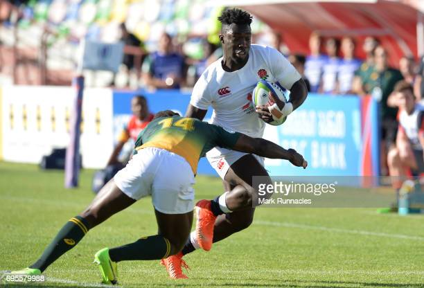 Gabriel Ibitoye of England is tackled by Yaw Penxe of South Africa during the World Rugby U20 Championship Semi Final match between England and South...