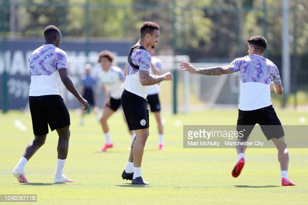 Gabriel Jesus and Joao Cancelo of Manchester City share a joke during the training session at Manchester City Football Academy on June 01 2020 in...