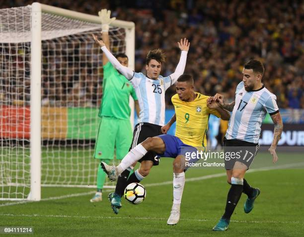 Gabriel Jesus of Brazil is challenged by Alejandro Dario Gomez and Nicolas Otamendi of Argentina during the Brazil Global Tour match between Brazil...