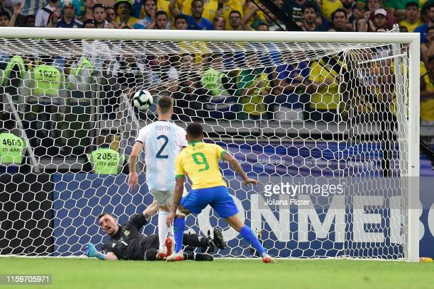 Gabriel Jesus of Brazil scores the opening goal against Franco Armani of Argentina during the Copa America Brazil 2019 Semi Final match between...