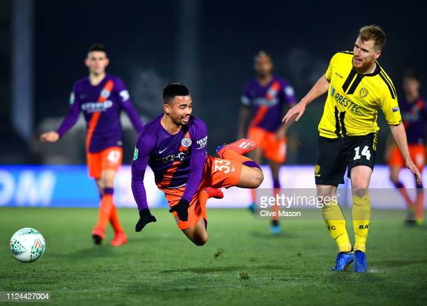 Gabriel Jesus of Manchester City is tackled by Damien McCrory of Burton Albion during the Carabao Cup Semi Final Second Leg match between Burton...