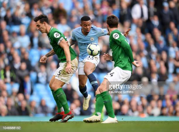 Gabriel Jesus of Manchester City is tackled by Lewis Dunk and Davy Propper of Brighton during the Premier League match between Manchester City and...