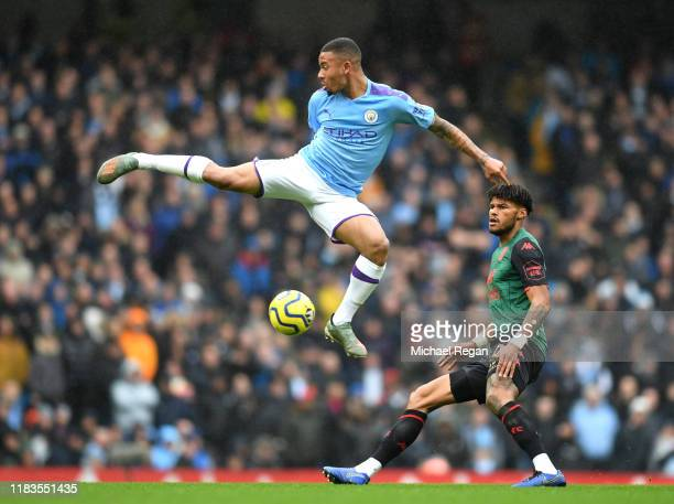 Gabriel Jesus of Manchester City jumps for the ball with Tyrone Mings of Aston Villa during the Premier League match between Manchester City and...
