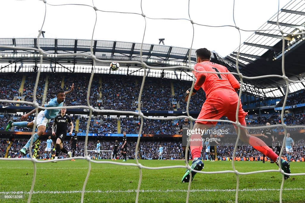 Gabriel Jesus of Manchester City scores his side's fifth goal past Lukasz Fabianski of Swansea City during the Premier League match between Manchester City and Swansea City at Etihad Stadium on April 22, 2018 in Manchester, England.
