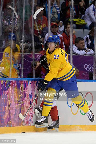 Gabriel Landeskog of Sweden checks Patrick Sharp of Canada during the first period of the men's ice hockey gold medal game Sochi 2014 Winter Olympics...