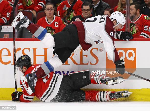 Gabriel Landeskog of the Colorado Avalanche and Connor Murphy of the Chicago Blackhawks get tangled up along the boards at the United Center on March...