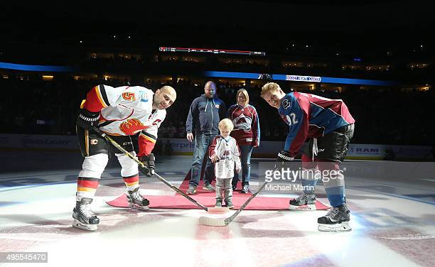 Gabriel Landeskog of the Colorado Avalanche and Mark Giordano of the Calgary Flames pose with fouryearold Owen for a ceremonial faceoff on Hockey...