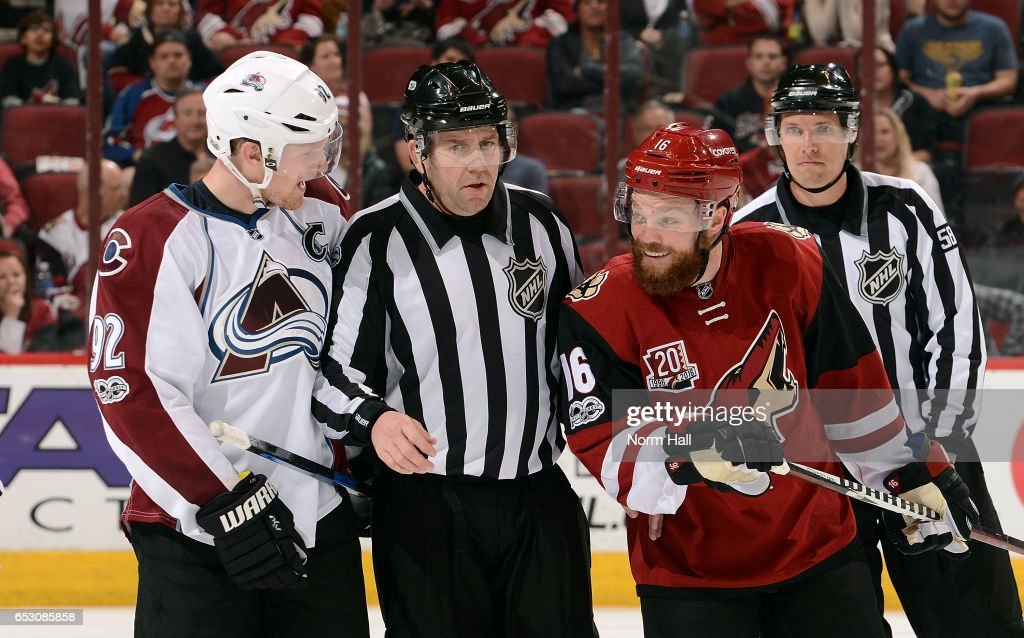 Gabriel Landeskog #92 of the Colorado Avalanche and Max Domi #16 of the Arizona Coyotes are separated by linesman Michel Cormier as they exchange words during the third period at Gila River Arena on March 13, 2017 in Glendale, Arizona.