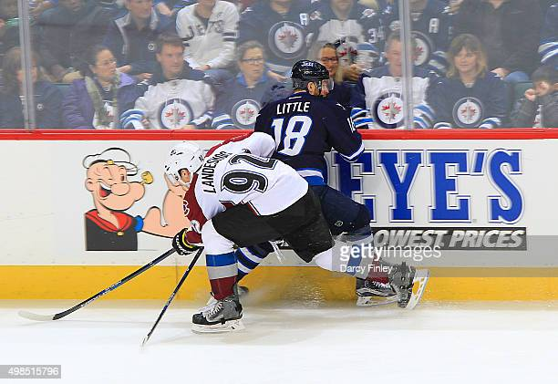 Gabriel Landeskog of the Colorado Avalanche checks Bryan Little of the Winnipeg Jets into the boards during second period action at the MTS Centre on...
