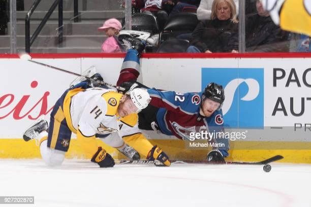 Gabriel Landeskog of the Colorado Avalanche falls to the ice along side Mattias Ekholm of the Nashville Predators at the Pepsi Center on March 4 2018...