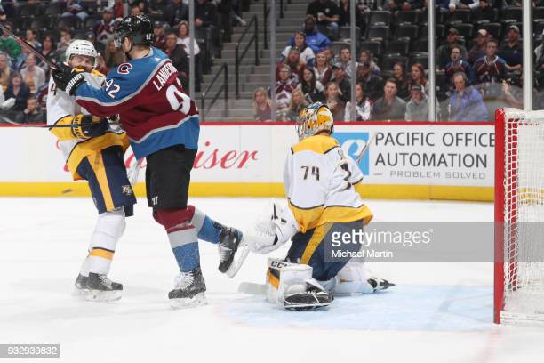Gabriel Landeskog of the Colorado Avalanche fights for position against Ryan Ellis of the Nashville Predators while a shot by Nathan MacKinnon is...