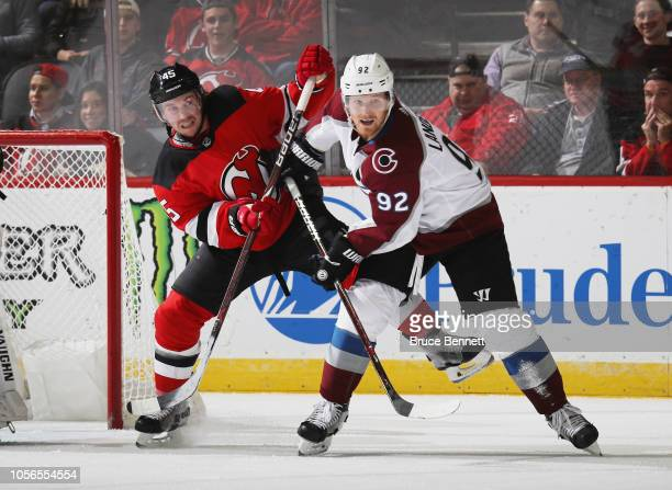 Gabriel Landeskog of the Colorado Avalanche is checked by Sami Vantanen of the New Jersey Devils at the Prudential Center on October 18 2018 in...