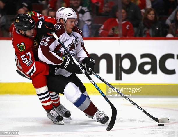 Gabriel Landeskog of the Colorado Avalanche is pressured by Trevor van Riemsdyk of the Chicago Blackhawks at the United Center on March 19 2017 in...