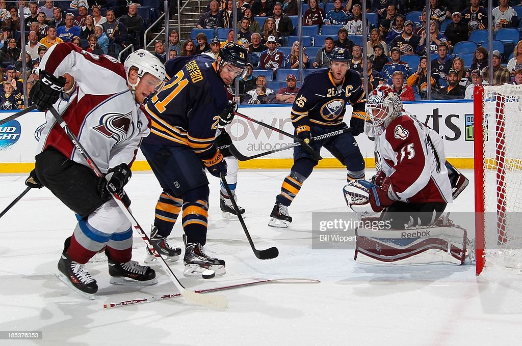 Gabriel Landeskog #22 of the Colorado Avalanche reaches for the puck against Drew Stafford #21 of the Buffalo Sabres as Avalanche goaltender Jean-Sebastien Giguere looks for his stick on October 19, 2013 at the First Niagara Center in Buffalo, New York. Colorado won, 4-2.