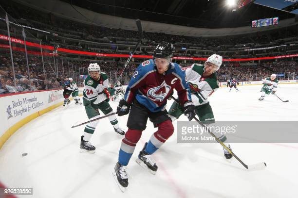 Gabriel Landeskog of the Colorado Avalanche reaches for the puck against Eric Staal and Matt Dumba of the Minnesota Wild at the Pepsi Center on March...