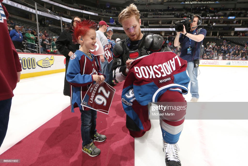 Gabriel Landeskog #92 of the Colorado Avalanche signs a jersey for a young fan after the teams last home game of the season at the Pepsi Center on April 6, 2017 in Denver, Colorado.