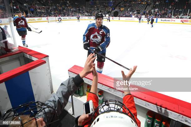 Gabriel Landeskog of the Colorado Avalanche tosses a puck to a fan on the bench during warm ups prior to the game against the Pittsburgh Penguins at...