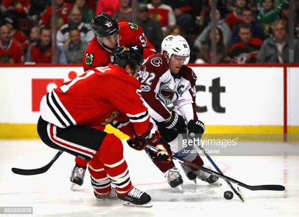 Gabriel Landeskog of the Colorado Avalanche tries to get off a shot between Brian Campbell and Trevor van Riemsdyk of the Chicago Blackhawks at the...