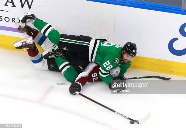 Gabriel Landeskog of the Colorado Avalanche tries to play the puck as he is hit by Stephen Johns of the Dallas Stars in the first period in a Western...