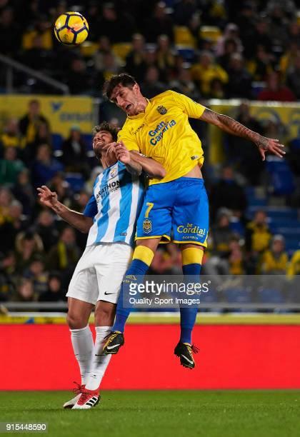 Gabriel Martin Penalba of Las Palmas competes for the ball with Adrian Gonzalez of Malaga during the La Liga match between Las Palmas and Malaga at...