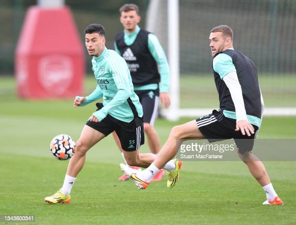 Gabriel Martinelli and Calum Chambers of Arsenal during a training session at London Colney on September 28, 2021 in St Albans, England.