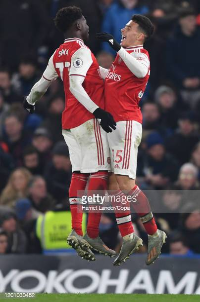 Gabriel Martinelli of Arsenal celebrates with teammate Bukayo Saka after scoring his team's first goal during the Premier League match between...