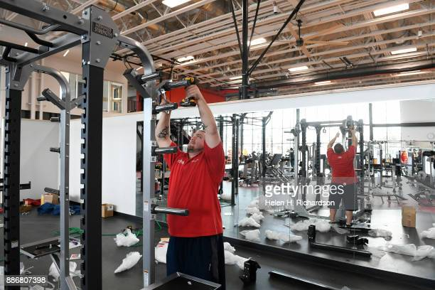 DENVER CO NOVEMBER 29 Gabriel Martinez works on installing a power rack weight system in the large cardio and fitness center at the new Carla Madison...