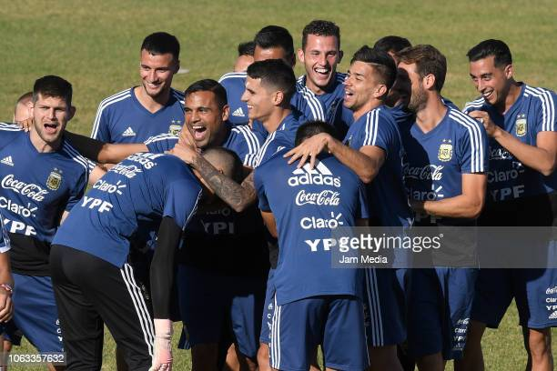 Gabriel Mercado Erick Lamella and Giovani Simeoni of Argentina embrace during a training session ahead of the international friendly match against...