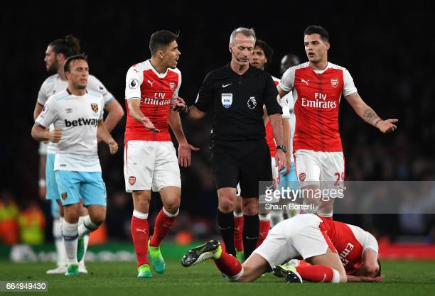 Gabriel of Arsenal and Granit Xhaka of Arsenal argue with referee Martin Atkinson during the Premier League match between Arsenal and West Ham United...