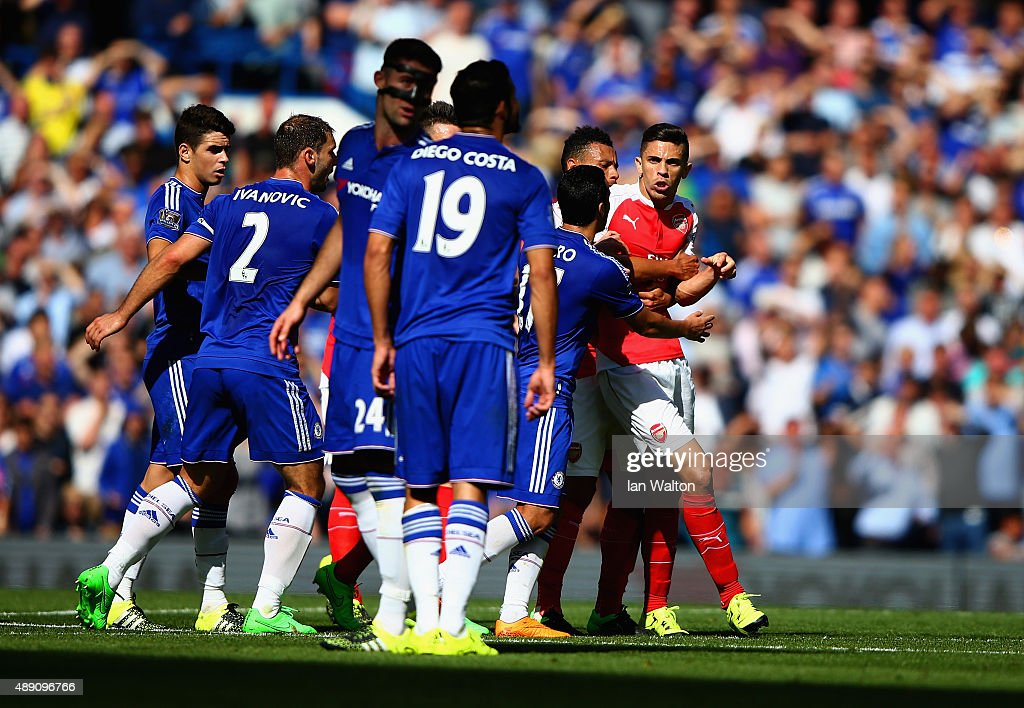 Gabriel (1st R) of Arsenal is blocked by Chelsea players as he tries to walk toward Diego Costa of Chelsea after being shown a red card during the Barclays Premier League match between Chelsea and Arsenal at Stamford Bridge on September 19, 2015 in London, United Kingdom.