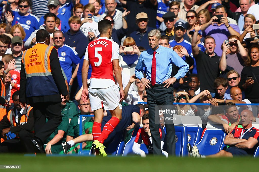 Gabriel of Arsenal walks off the pitch in front of Head coach Arsene Wenger as he is shown a red card during the Barclays Premier League match between Chelsea and Arsenal at Stamford Bridge on September 19, 2015 in London, United Kingdom.
