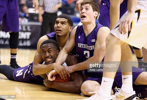 Gabriel Olaseni of the Iowa Hawkeyes and Samjay Lumpkin and Dave Sobolewski of the Northwestern Wildcats battle for a loose ball during the first...