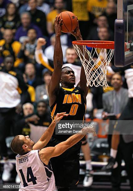 Gabriel Olaseni of the Iowa Hawkeyes dunks over Tre Demps of the Northwestern Wildcats at WelshRyan Arena on January 25 2014 in Evanston Illinois...