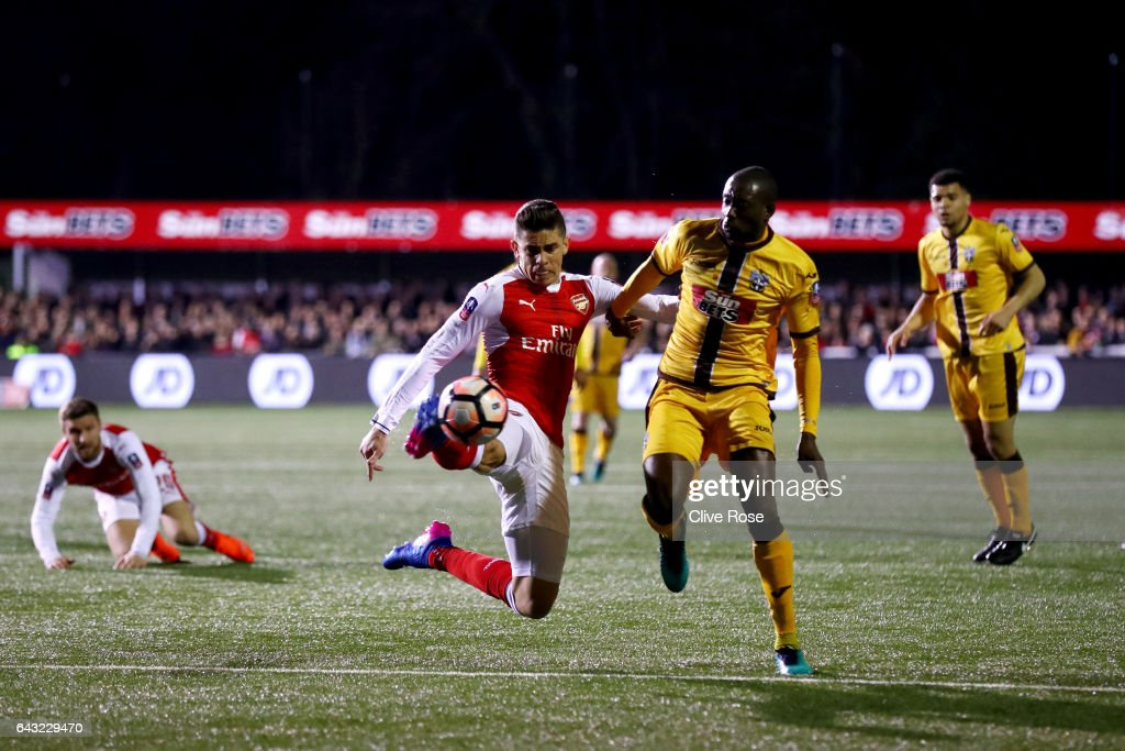 Gabriel Paulista of Arsenal clears the ball under pressure from Bedsente Gomis of Sutton United during the Emirates FA Cup fifth round match between Sutton United and Arsenal on February 20, 2017 in Sutton, Greater London.
