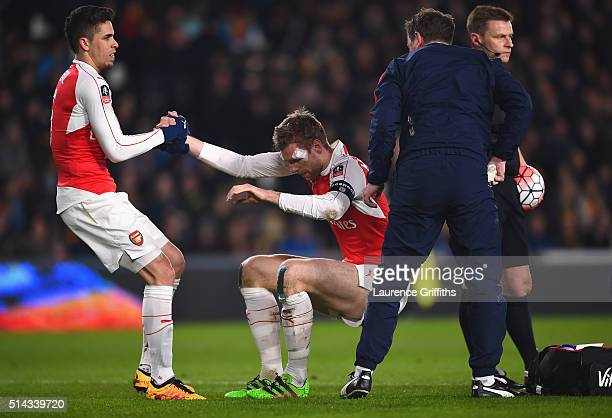 Gabriel Paulista of Arsenal helps Per Mertesacker to his feet after a clash of heads during the Emirates FA Cup Fifth Round Replay match between Hull...