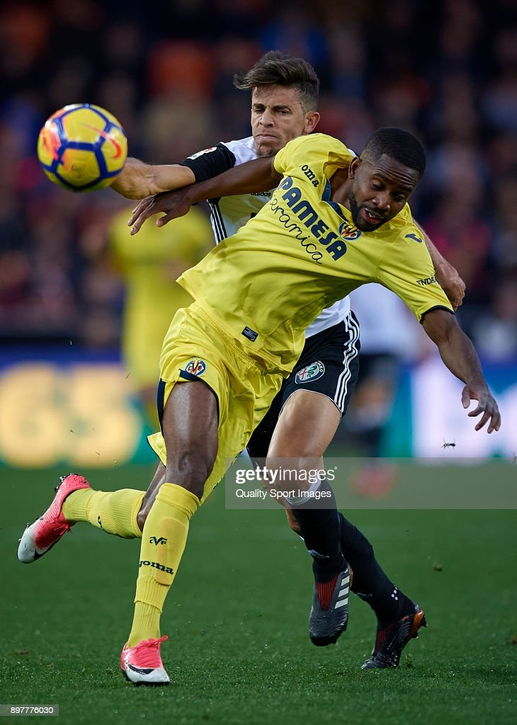 Gabriel Paulista (L) of Valencia competes for the ball with Cedric Bakambu of Villarreal during the La Liga match between Valencia and Villarreal at Mestalla Stadium on December 23, 2017 in Valencia, Spain.